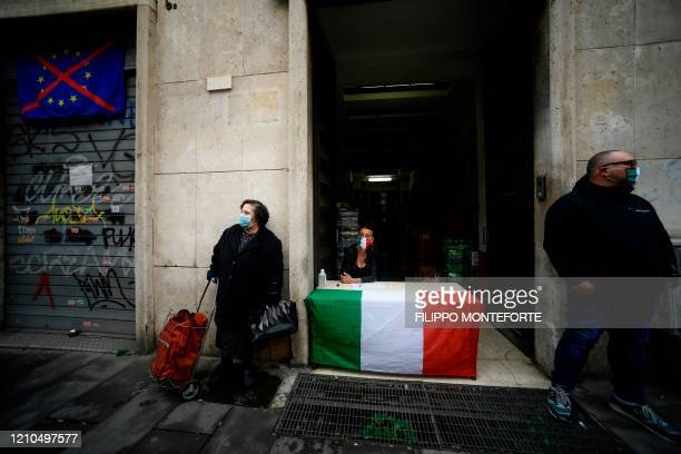 Woman wearing a face mask waits with her trolley for free shopping distributed by activists of Italian neo-fascist movement Casapound on April 21,...