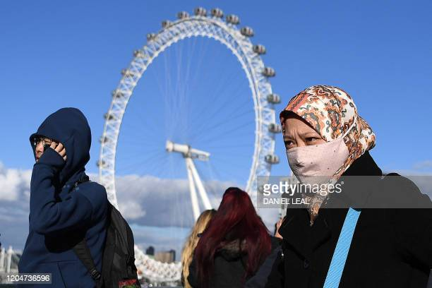 TOPSHOT A woman wearing a face mask walks across Westminster Bridge near the London Eye landmark in central London on March 2 2020 Britain's Prime...