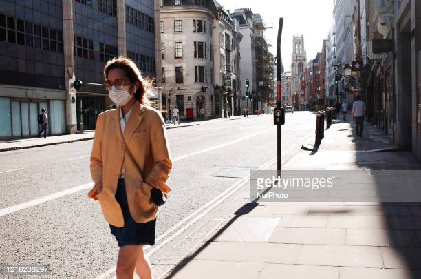 A woman wearing a face mask walks along a neardeserted Fleet Street in London England on May 29 2020 The UK is now in its tenth week of coronavirus...