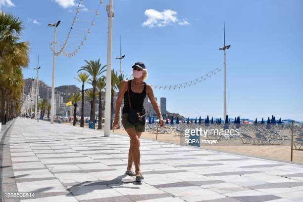 Woman wearing a face mask walks along Benidorm's promenade amid Coronavirus crisis. When Spain locked down to slow the coronavirus in March, about...