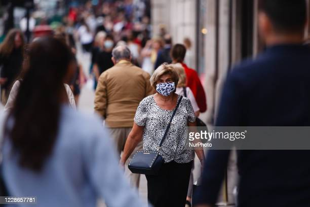 Woman wearing a face mask walks along Regent Street in London, England, on September 22, 2020. British Prime Minister Boris Johnson this afternoon...