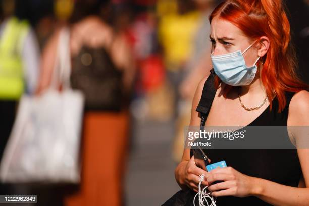 Woman wearing a face mask walks amid shoppers on Oxford Street in heatwave conditions in London, England, on June 25, 2020. Temperatures rose to 33C...