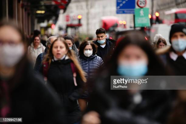 Woman wearing a face mask walks amid shoppers on Regent Street in London, England, on December 4, 2020. London has returned to so-called Tier 2 or...