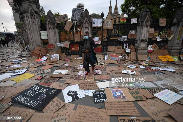 A woman wearing a face mask walks among BLM placards and signs left outside the Houses of Parliament during a Black Lives Matter protest in...