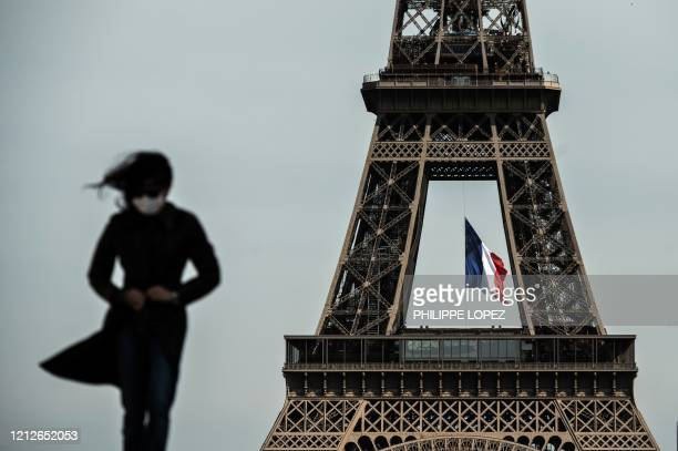 Woman wearing a face mask walks as a French national flag flies on the Eiffel Tower in background in Paris on May 11, 2020 on the first day of...