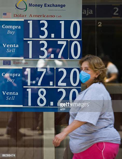 A woman wearing a face mask walks by a board displaying the exchange rate between the dollar and the Mexican peso on the window of a bank in Mexico...