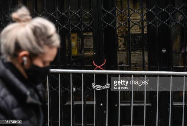 Woman wearing a face mask walks by a closed business premises in Dublin's city center during Level 5 Covid-19 lockdown. On Monday, 15 March 2021, in...