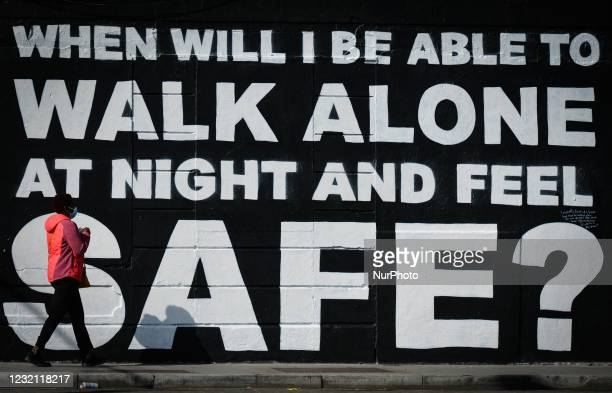Woman wearing a face mask walks by a mural by Irish artist Emmalene in Dublin's city centre during level 5 COVID-19 lockdown. The inscription 'When...