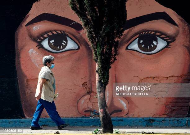 Woman wearing a face mask walks by a mural on one of the walls of the San Nicolas Tolentino cemetery in the municipality of Iztapalapa in Mexico City...