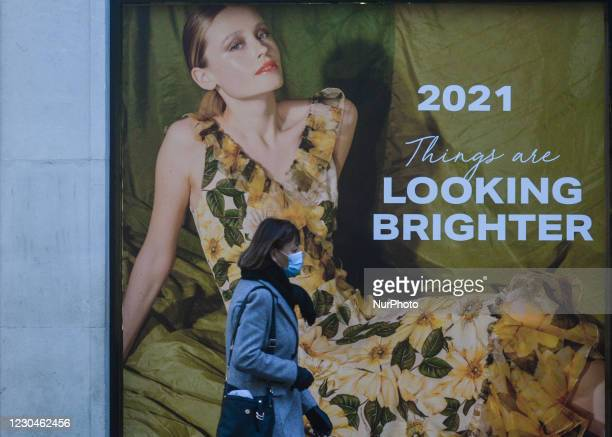 Woman wearing a face mask walks by a new Brown Thomas' windows on Grafton Street, in Dublin city center. Ireland is going back into a full lockdown...