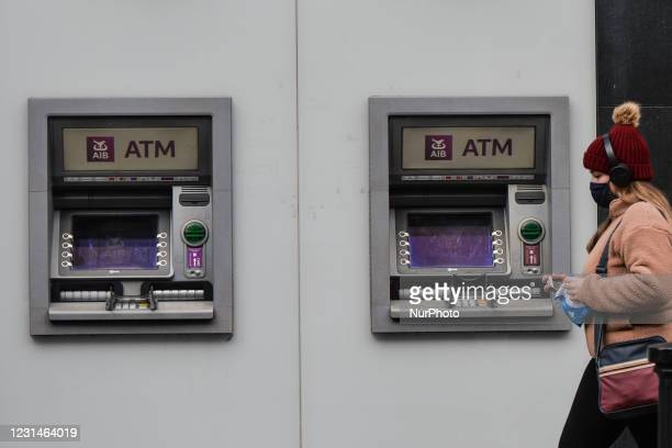 Woman wearing a face mask walks by an AIB ATM in Dublin city center during Level 5 COVID-19 lockdown. The Bank of Ireland announced today the closure...