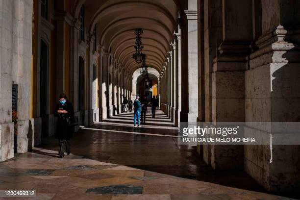 Woman wearing a face mask walks by Rua Augusta arch in Lisbon on January 7, 2021. - Portugal reported a record 10,000 new coronavirus cases in 24...