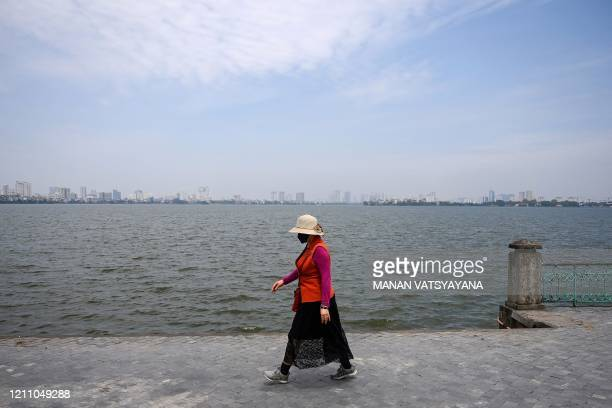 A woman wearing a face mask walks by the West Lake in Hanoi on April 27 after Vietnam eased its nationwide social isolation effort to prevent the...