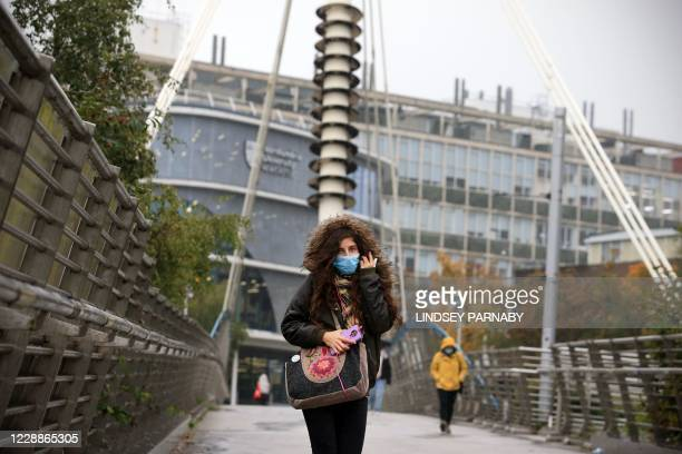 Woman wearing a face mask walks close to Northumbria University in Newcastle-upon-Tyne, north-east England on October 3, 2020 as many students...