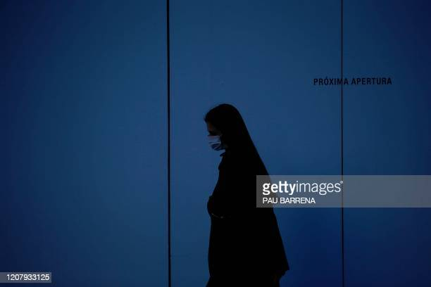 Woman wearing a face mask walks in Barcelona on March 21, 2020 during a national lockdown to prevent the spread of the new coronavirus. - Spain...