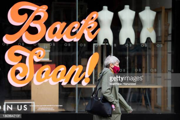 """Woman wearing a face mask walks in front of a shop with a """"back soon"""" sign in the window on February 22, 2021 in Cardiff, Wales. Wales First Minister..."""