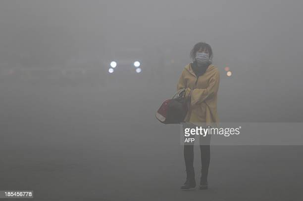 A woman wearing a face mask walks in heavy smog in Harbin northeast China's Heilongjiang province on October 21 2013 Choking clouds of pollution...