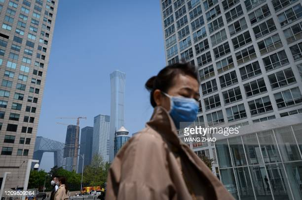 Woman wearing a face mask walks in the Central Business District in Beijing on April 14, 2020.