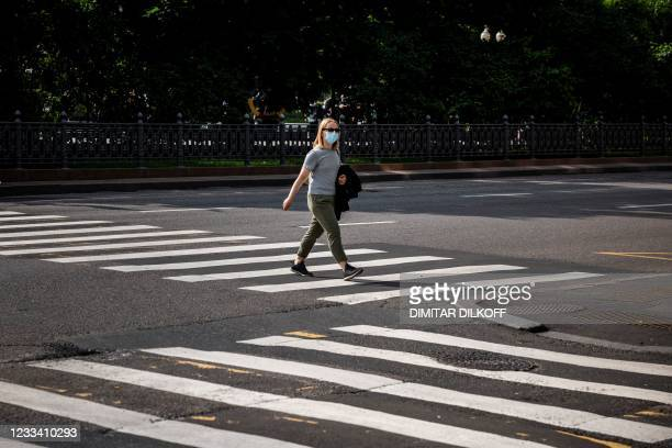 """Woman wearing a face mask walks on a pedestrian crossing in Moscow, on June 12, 2021 as Moscow mayor Sergei Sobyanin announced a """"non-working"""" week..."""