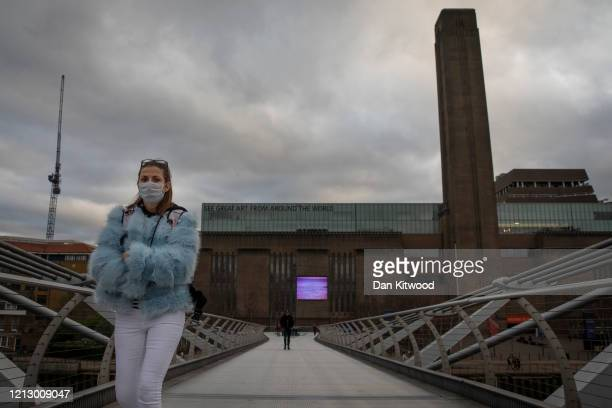 Woman wearing a face mask walks over Millennium Bridge near the Tate Modern on March 17, 2020 in London, England. The Tate Modern has announced it...
