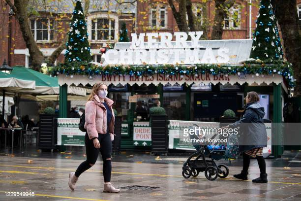 Woman wearing a face mask walks past a cafe with a 'Happy Christmas' sign on The Hayes on November 9, 2020 in Cardiff, Wales. Wales' health minister...