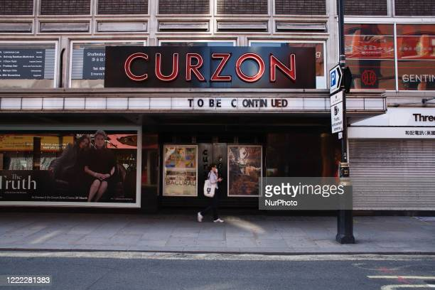 Woman wearing a face mask walks past a closed branch of cinema chain Curzon on Shaftesbury Avenue in London, England, on June 23, 2020. British Prime...