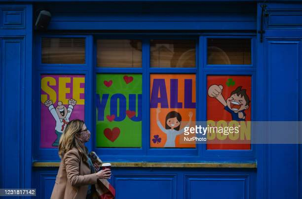 Woman wearing a face mask walks past a closed business premises with a message in the window reading 'See You All Soon' - a street scene seen in...
