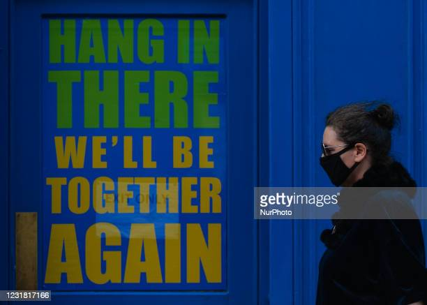 Woman wearing a face mask walks past a closed business premises with a message in the window reading 'Hang In There, We'll Be Together Again' - a...
