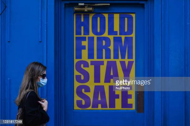 Woman wearing a face mask walks past a closed business premises with a message in the window reading 'Hold Firm Stay Safe' - a street scene seen in...