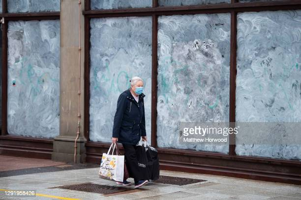 Woman wearing a face mask walks past a closed shop on December 18 in Cardiff, Wales. A two-household limit will be in place from December 23 to...