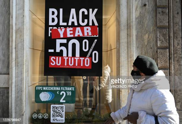 "Woman wearing a face mask walks past a clothing shop displaying a poster reading ""Black Year"" , ""50 percent discount on everything"" on November 26,..."