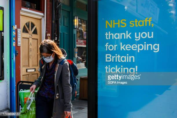 A woman wearing a face mask walks past a Coronavirus public information campaign poster saying 'NHS Staff thank you for keeping Britain ticking' in...