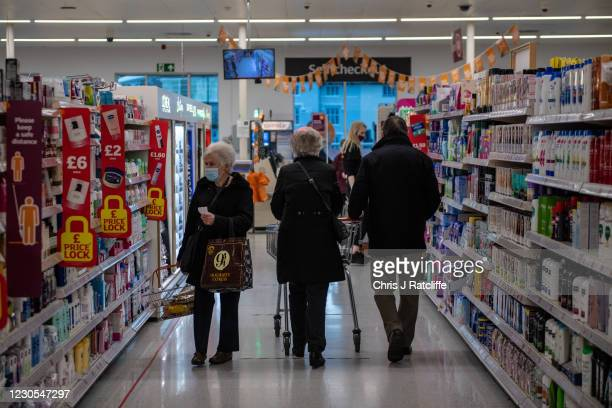 Woman wearing a face mask walks past a couple who are shopping together in a Sainsburys supermarket on January 12, 2021 in Maidstone, United Kingdom....