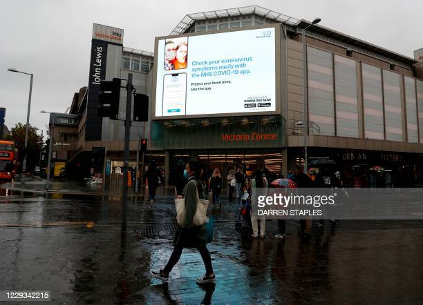 Woman wearing a face mask walks past a digital display for the NHS Covid-19 app in Nottingham, central England as the city moves into Covid-19 Tier 3...