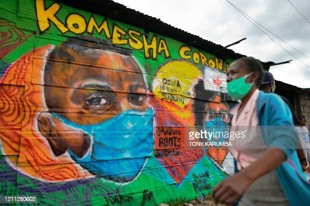 Woman wearing a face mask walks past a mural advocating safety practices to curb the spread of the novel coronavirus at Mathare slum April 29, 2020...