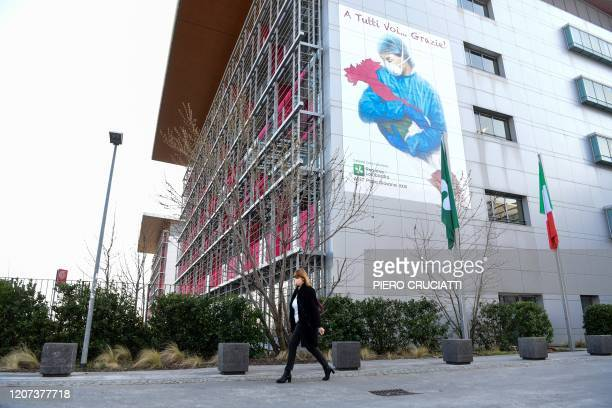 Woman wearing a face mask walks past a mural by artist Franco Rivolli Art, depicting a nurse wearing a face mask, with wings behind her back and...