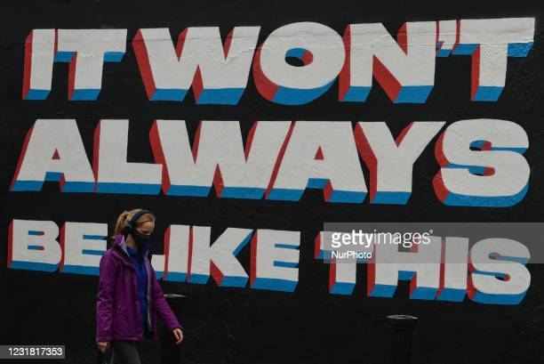 Woman wearing a face mask walks past a mural by Irish artist Emmalene Blake in Dublin's city centre during level 5 COVID-19 lockdown. The theme of...