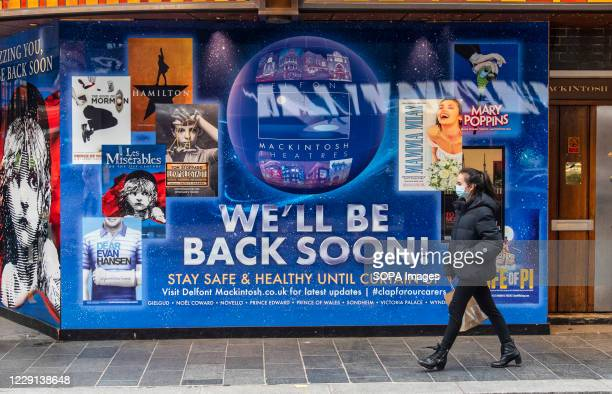 Woman wearing a face mask walks past a new signage with Well be back soon on the Sondheim theatre completed after Producer Cameron Mackintosh...