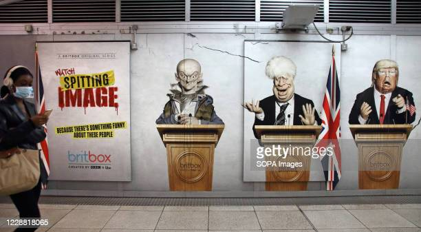 Woman wearing a face mask walks past a panel featuring Political advisor Dominic Cummings, UK Prime Minister Boris Johnson and US President Donald...