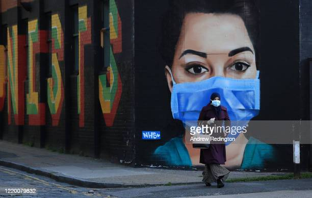 Woman wearing a face mask walks past a piece of street art depicting an NHS worker on April 21, 2020 in the Shoreditch area of London, England. The...