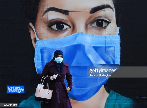 A woman wearing a face mask walks past a piece of street art depicting an NHS worker on April 21 2020 in the Shoreditch area of London England The...