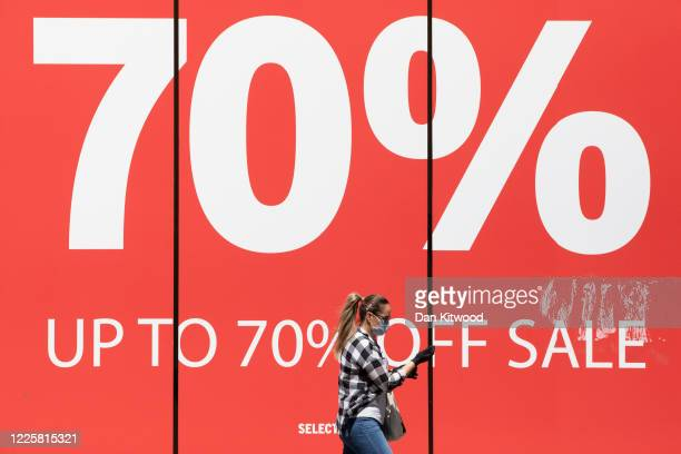 A woman wearing a face mask walks past a sale sign on Oxford Street on May 19 2020 in London England As shops gear up to open after a long period of...