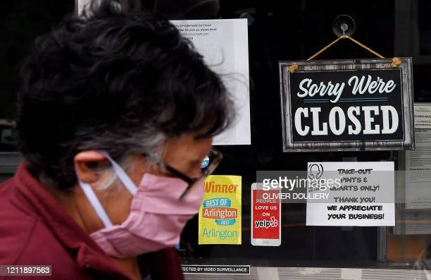 A woman wearing a face mask walks past a sign in the window of a food store announces that the business is closed during a shelter in place lockdown...
