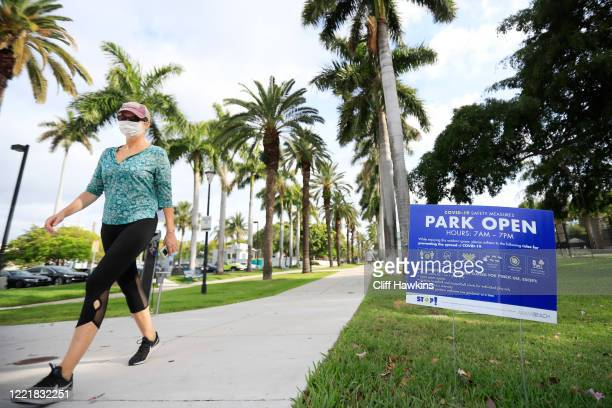 A woman wearing a face mask walks past a sign indicates that Flamingo Park is open and COVID19 safety measures that apply on April 29 2020 in Miami...