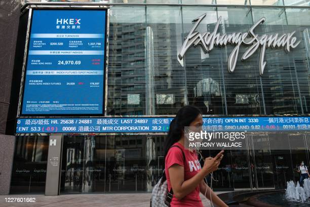A woman wearing a face mask walks past a stocks display board outside Exchange Square in Hong Kong on July 16 as the city experiences another spike...