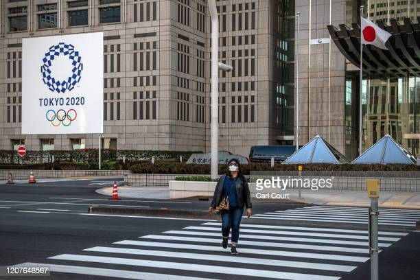 Woman wearing a face mask walks past a Tokyo 2020 Olympics banner displayed on the side of a building on March 19, 2020 in Tokyo, Japan. As Japanese...