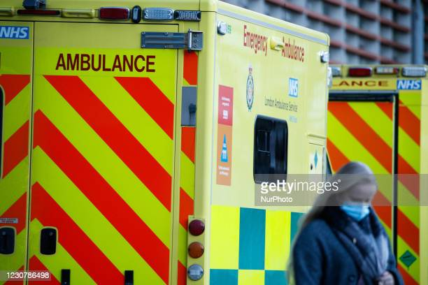 Woman wearing a face mask walks past ambulances outside the emergency department of the Royal London Hospital in London, England, on January 25,...