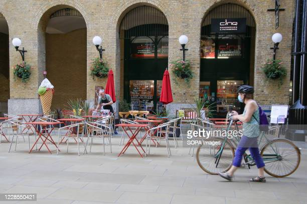 Woman wearing a face mask walks past an empty restaurant in Hay's Galleria in London which would normally be busy with tourists and city workers. In...