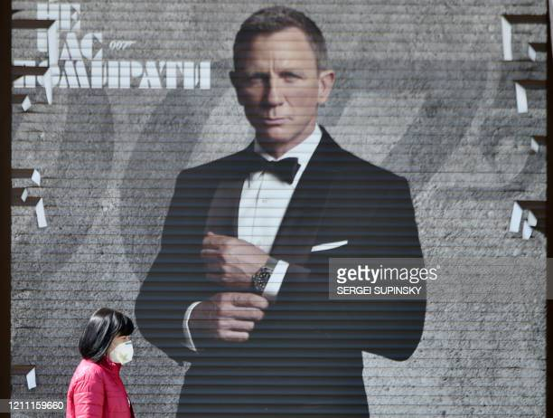 Woman wearing a face mask walks past an image of James Bond actor Daniel Craig in a shop window in the Ukrainian capital of Kiev on April 28 amid the...