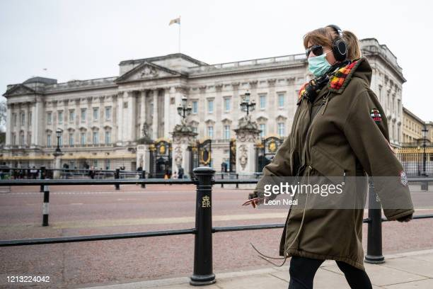 Woman wearing a face mask walks past Buckingham Palace on the day that Queen Elizabeth II is set to move to Windsor Palace in a bid to avoid the...
